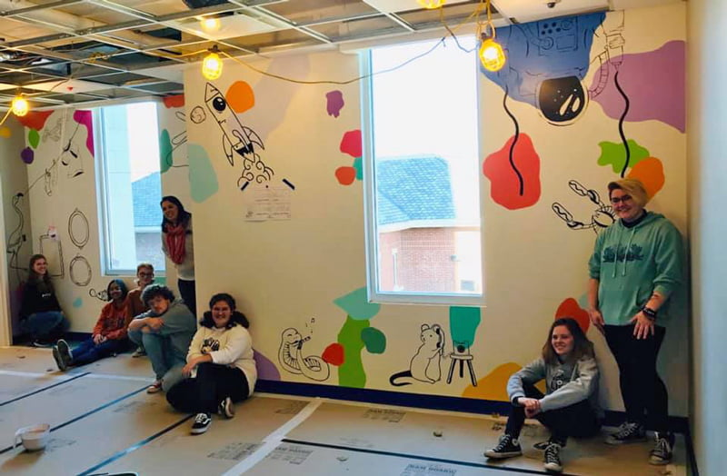Washington High School faculty and students hand-paint their mural in Dax's Playroom at the Peoria Ronald McDonald House® in Peoria, Illinois.